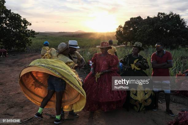 A group of costumed women reacts to a hug from a friend while they await the presentation of Maracatu in the city of Nazaré da Mata in Northeast...