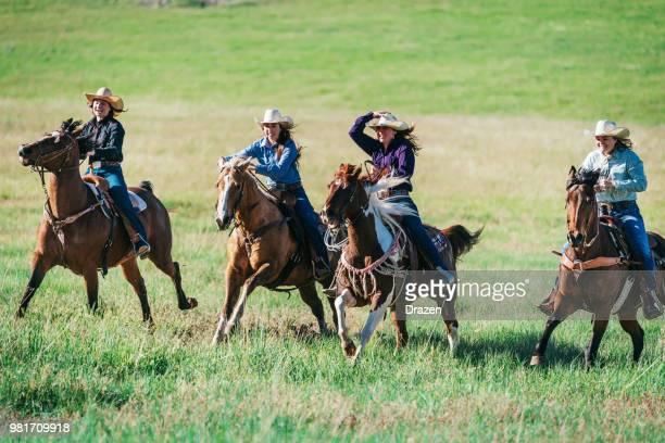groupe de cowgirls chevauchant des chevaux au galop - cowgirl photos et images de collection