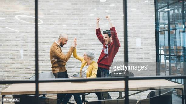 Group of coworkers cheering excitedly