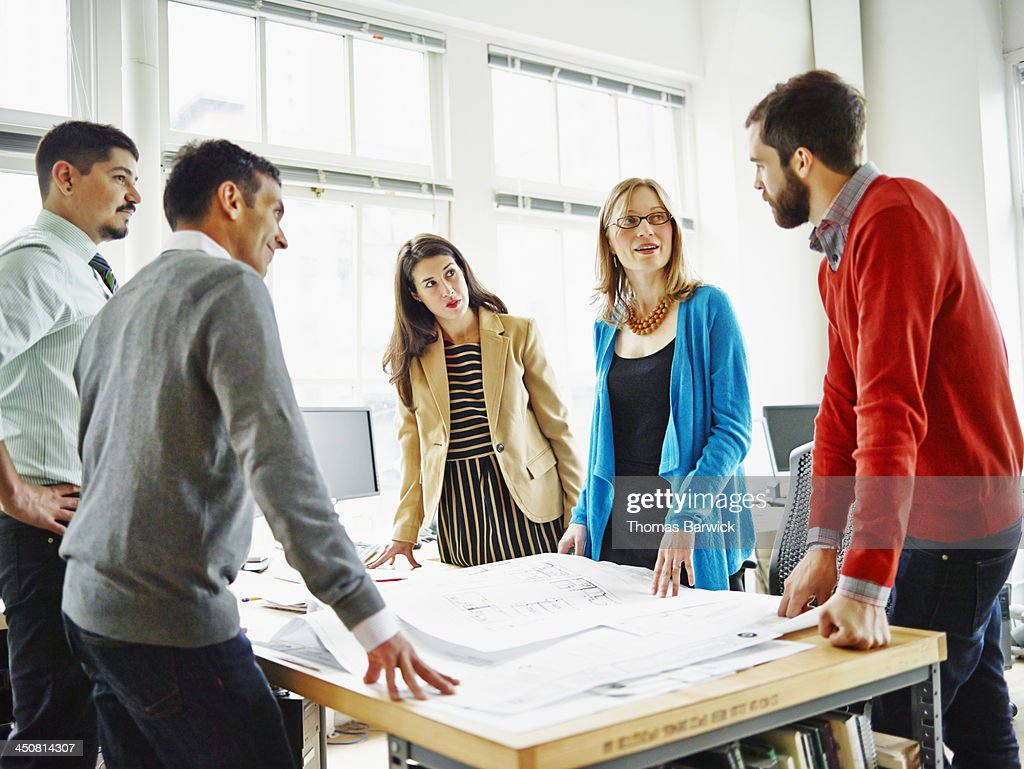 Group of coworkers discussing project in office : Stock Photo