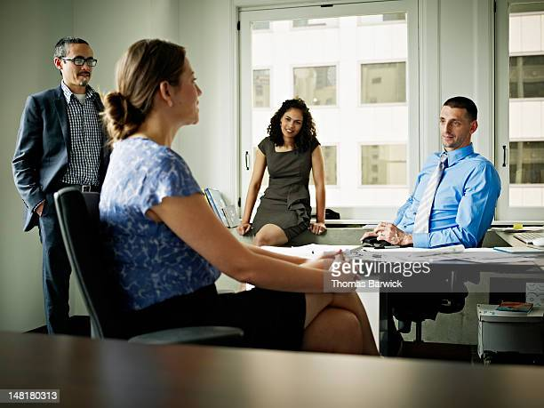 Group of coworkers in discussion at workstation