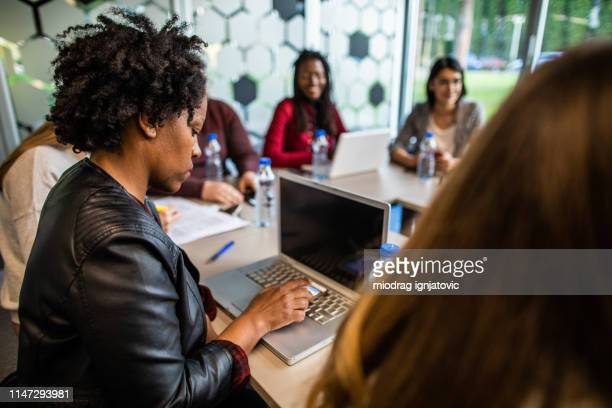group of coworkers on meeting in board room - economist stock pictures, royalty-free photos & images