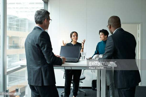 group of co-workers standing around desk and having meeting - ergonomics stock photos and pictures