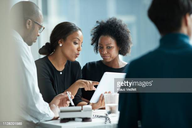 group of co-workers standing around desk and having meeting - business finance and industry stock pictures, royalty-free photos & images