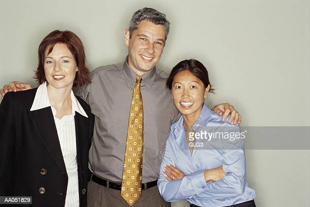 Group of co-workers with arms around each other, portrait