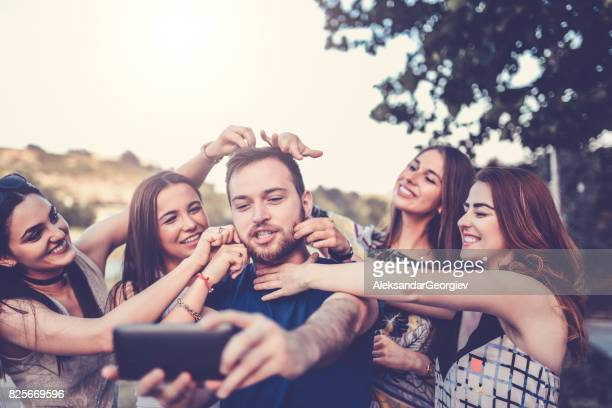 group of crazy friends taking selfie and making faces outdoors - spanking adult stock photos and pictures