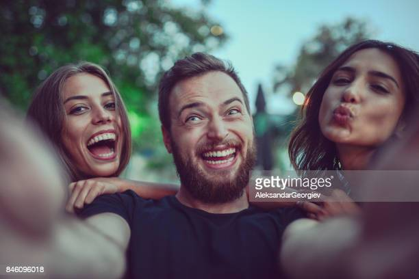 Group of Crazy Friends Taking Selfie and Making Faces Outdoors