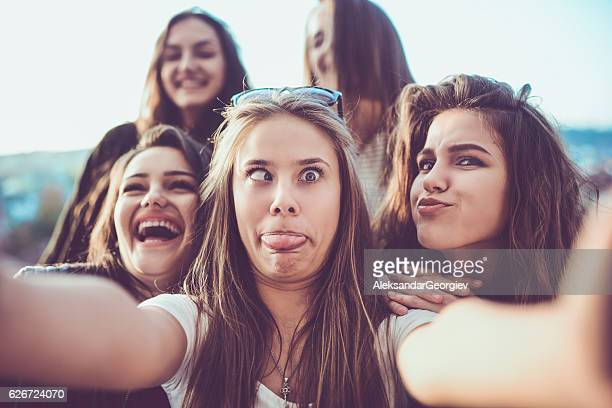 group of crazy girls taking selfie and making faces outdoors - bizarre stock pictures, royalty-free photos & images