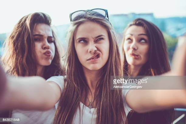 group of crazy girls taking selfie and making faces outdoors - making a face stock pictures, royalty-free photos & images