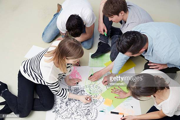 Group of creative professionals working on floor
