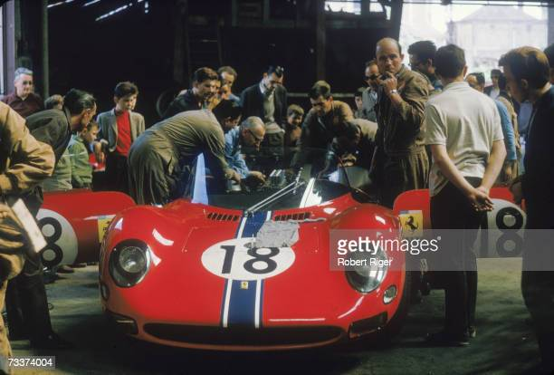 Group of crew members and spectators inspect the 1965 Ferrari 365 P2 racing car driven by Italian Nino Vaccarella and Mexican Pedro Rodriguez for the...