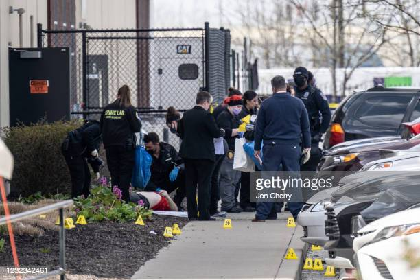 Group of crime scene investigators gather around a body in the parking lot of a FedEx SmartPost on April 16, 2021 in Indianapolis, Indiana. The area...