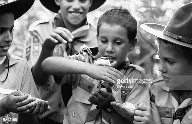 Group of cub scouts playing with field mice, outdoors (B&W)