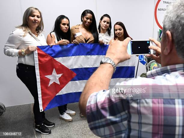 A group of Cuban doctors pose for a picture at Brasilia's airport Brazil before embarking and fly back to Cuba on November 22 2018 The Cuban...