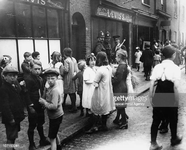 A group of curious children outside a shop as police investigate a murder on Hare Street Bethnal Green London July 1922