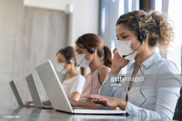 group of customer service representatives working at a call center wearing facemask - customer service representative stock pictures, royalty-free photos & images