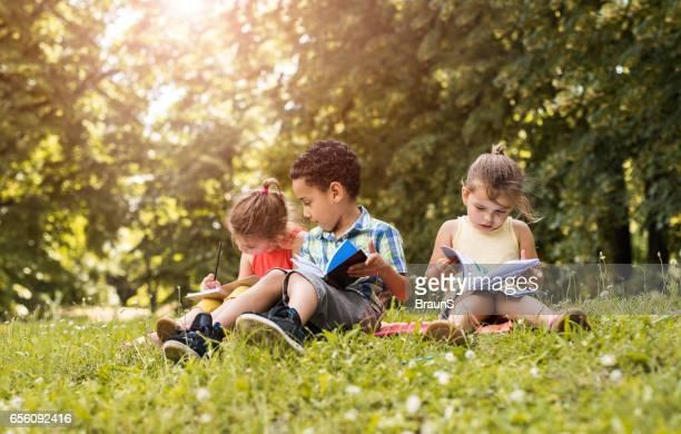 Grupo de niños lindos con los portátiles en el parque.
