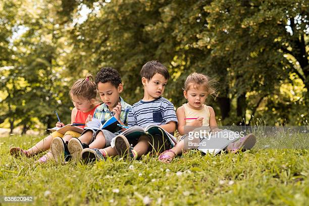 Group of cute kids writing in notebooks at the park.