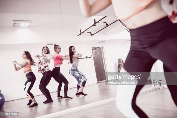group of cute smiling females training zumba in front of the mirror in gym - belly dancing stock photos and pictures