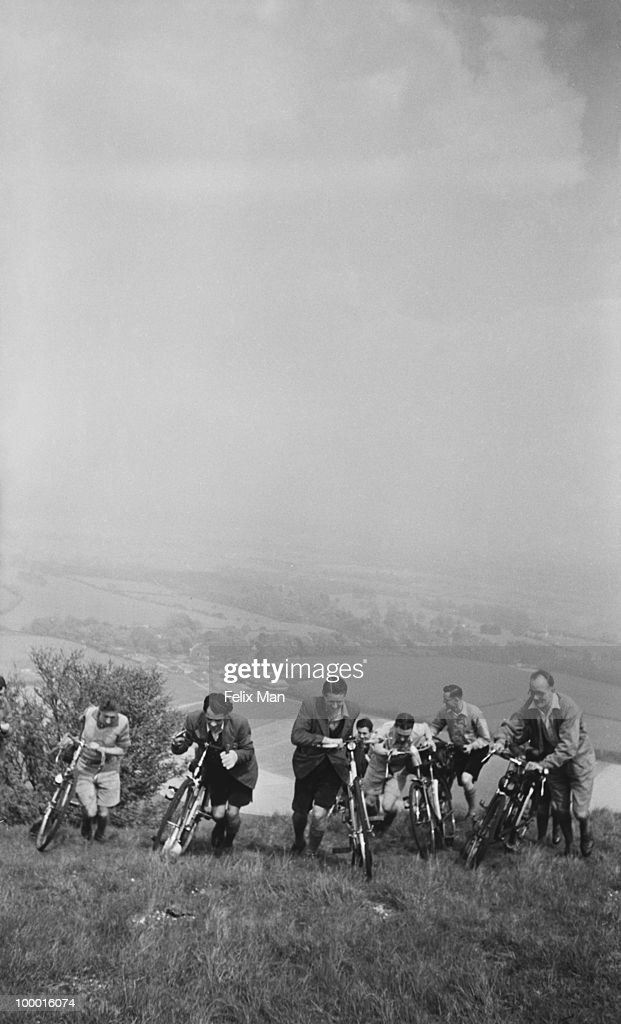 A group of cycling enthusiasts get off and push their bicycles to the top of Ditchling Beacon in Sussex, June 1939. Original publication: Picture Post - 151 - A Day Awheel - pub. 10th June 1939