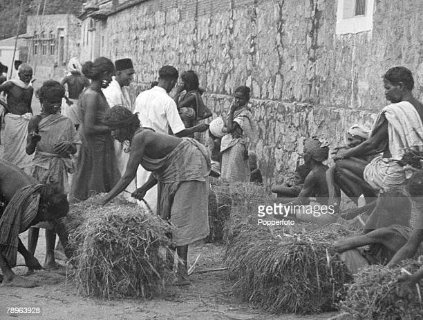 Group of Dalit women selling grass, which can be eaten by cows owned by men of caste, at a street market in India, circa 1940. The women, because of...