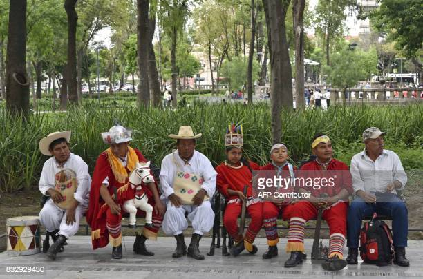 A group of dancers dressed in traditional customes sit in a bench at the Alameda Park in front of Foreign Ministry building during a protest against...