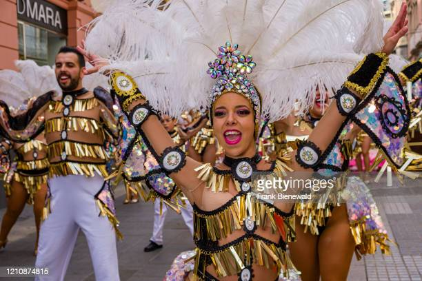 Group of dancers in colorful dresses and smiling, dancing in the streets during the Daytime Carnival.