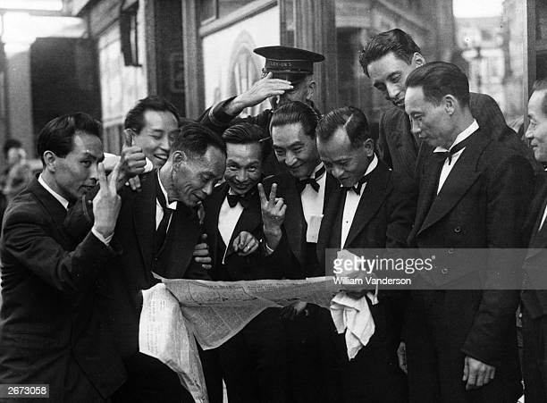 A group of delighted Chinese waiters read about Japan's surrender in a newspaper in London's West End
