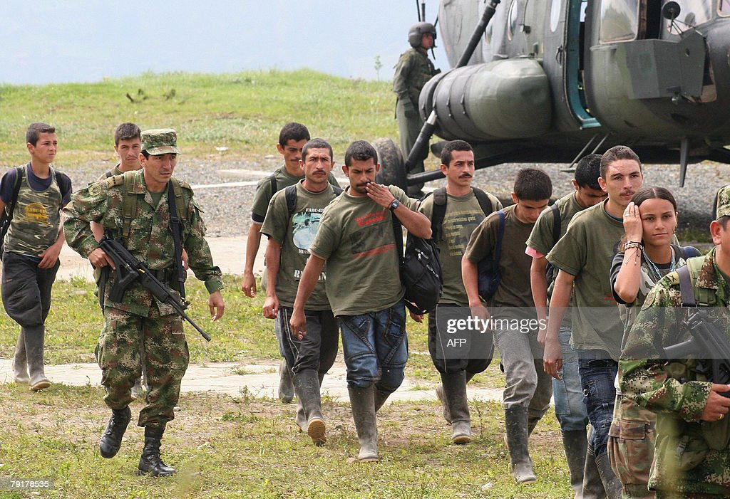 A group of demobilized fighters of the 47th Column of the FARC leftist guerrillas disembark from a military helicopter 23 January, 2008 at the Colombian Army Ayacucho Battalion compound in Manizalez, department of Caldas, Colombia. Thirteen FARC guerrillas of the 47th Column surrendered their weapons Wednesday to the army.