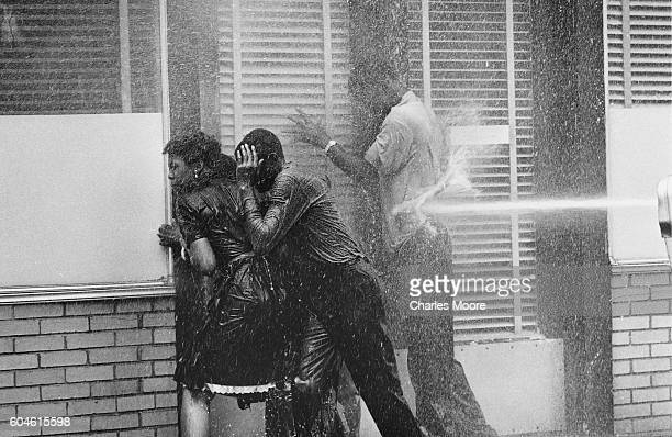 A group of demonstrators are pushed against a doorway by the water from a firehouse Birmingham Alabama May 3 1963 Police officers used both firehoses...