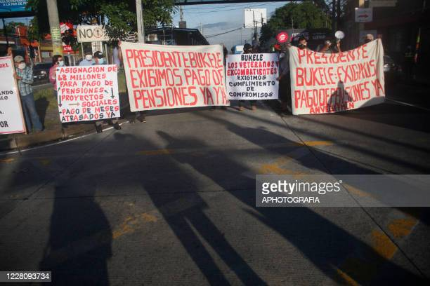 A group of demonstrators block a street holding signs demanding President Bukele their pensions payment during a veterans protest from the former...