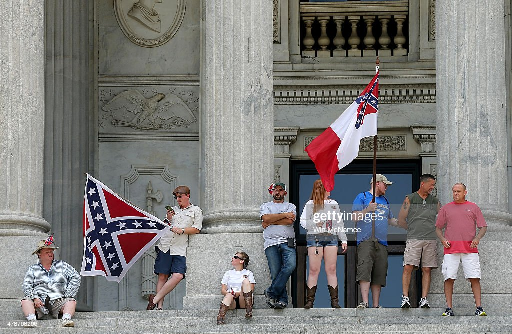 A group of demonstrators demonstrates at the top of the steps of the South Carolina State House while calling for the Confederate flag to remain on the State House grounds June 27, 2015 in Columbia, South Carolina. Earlier in the week South Carolina Gov. Nikki Haley expressed support for removing the Confederate flag from the State House grounds in the wake of the nine murders at Mother Emanuel A.M.E. Church in Charleston, South Carolina.