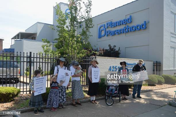 A group of demonstrators display signs during a prolife rally outside the Planned Parenthood Reproductive Health Center on June 4 2019 in St Louis...