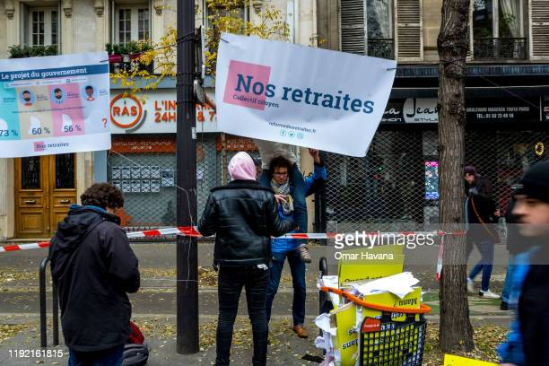 A group of demonstrators hang banners with messages related to pensions during the first day of an indefinite general strike on December 05 2019 in...