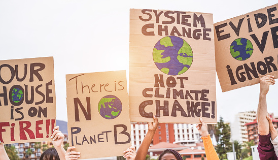 Group of demonstrators on road, young people from different culture and race fight for climate change - Global warming and enviroment concept - Focus on banners 1147070895