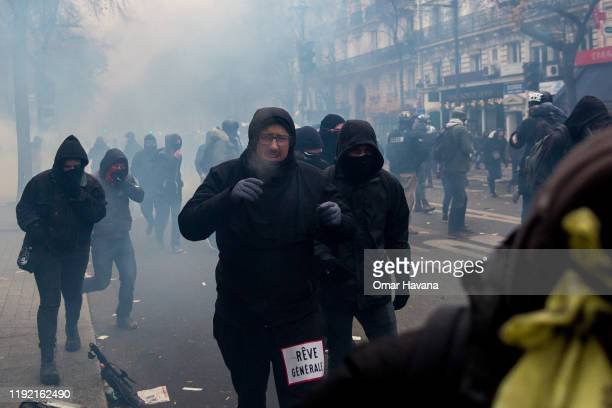 A group of demonstrators run from a police charge where they have thrown tear gas during the first day of an indefinite general strike on December 05...