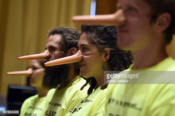 A group of demonstrators wearing Pinnochio noses take part in a silent protest as US Trade Representative Michael Froman testifies before a full...