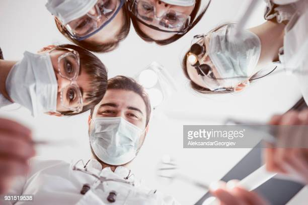 Group of Dental Doctors Work On Patient in Clinic