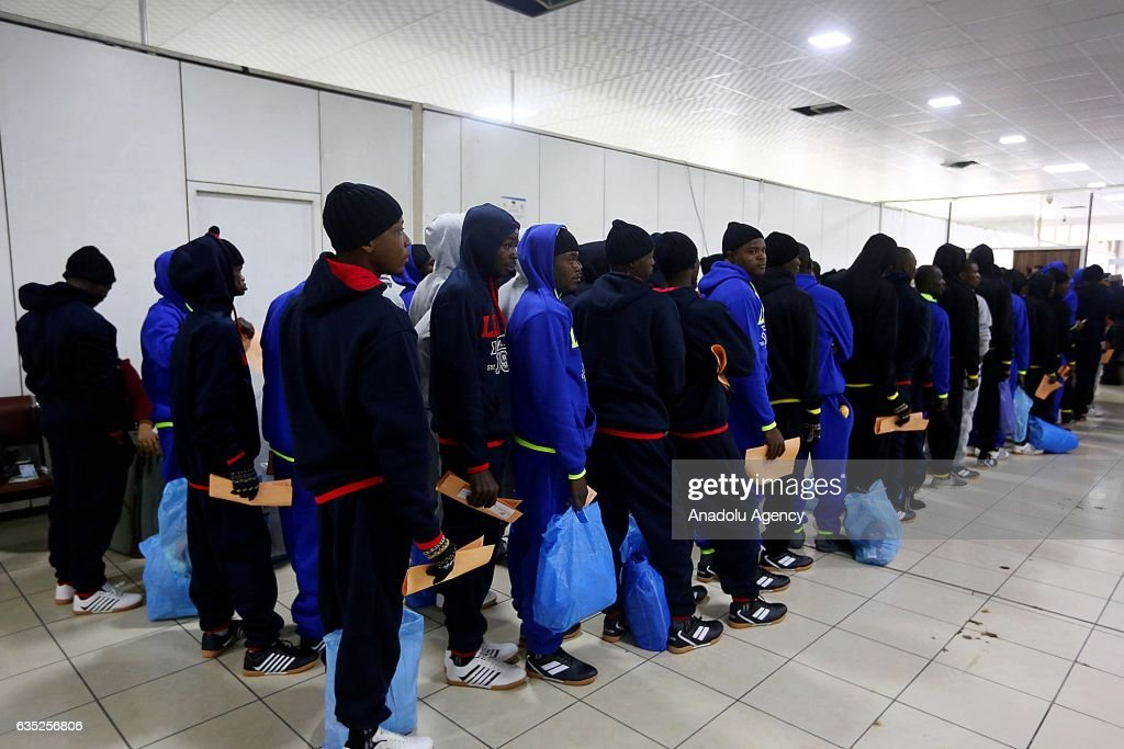 A group of deportee illegal immigrants wait before boarding to a plane, heading to Nigeria during their deportation at Mitiga International Airport in Tripoli, Libya on February 14, 2017. Approximately 171 Nigerian illegal immigrants are deported after the official process.