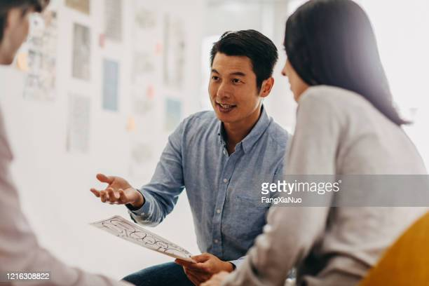 group of design professionals talking at meeting in modern office studio - korean ethnicity stock pictures, royalty-free photos & images