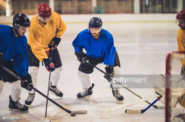 Group of determined ice hockey players tackling during a match at rink.