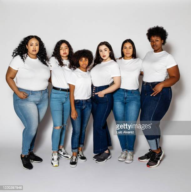 group of different size women posing in studio - jeans stock pictures, royalty-free photos & images