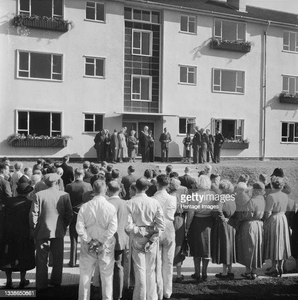 Group of dignitaries stood outside the 2000th post-war Easiform dwelling in Plymouth on its ceremonial opening day, with a crowd of people in the...