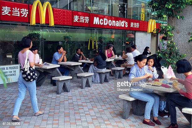 A group of diners eating in the outdoor dining area at a popular McDonalds Restaurant in Singapore