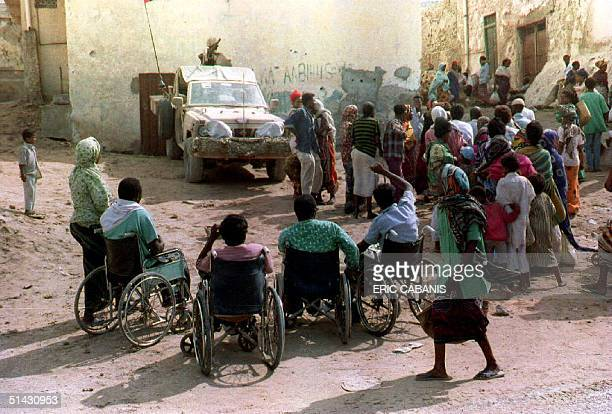 A group of disabled Somalis wait for food distribution in the old district of Hamarweyn in Mogadishu Somalia 05 July 1993 as UN soldiers from the...