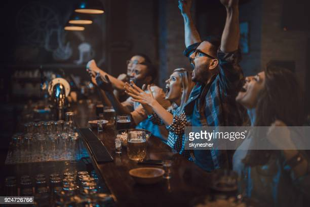 group of disappointed fans watching a sports game on tv in a bar. - mens world championship stock photos and pictures