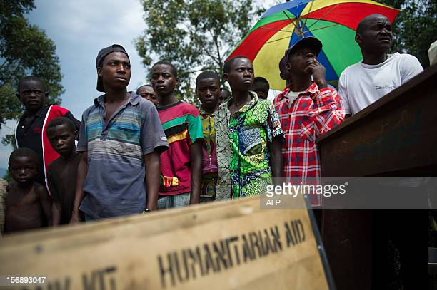 A group of displaced Congolese men and boys stand waiting for humanitarian aid in a camp for the internally displaced in Mugunga 8km west of Goma in...