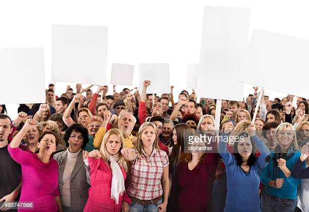 group of displeased people holding banners and looking at camera - protest stockfoto's en -beelden