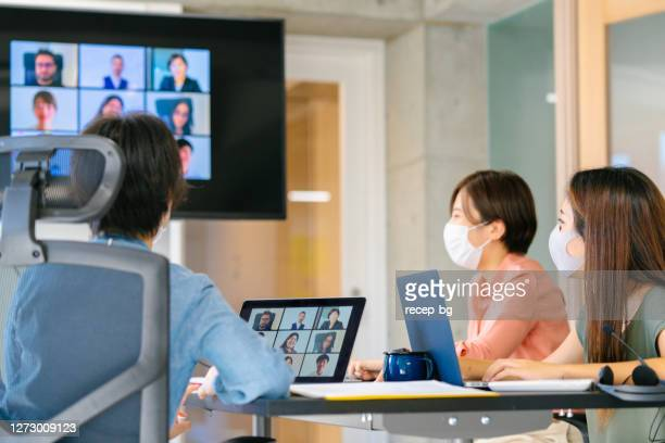 ビデオ電話会議を通じてグローバルビジネスミーティングを行う多様なビジネス・ピープルのグループ - ミーティング ストックフォトと画像