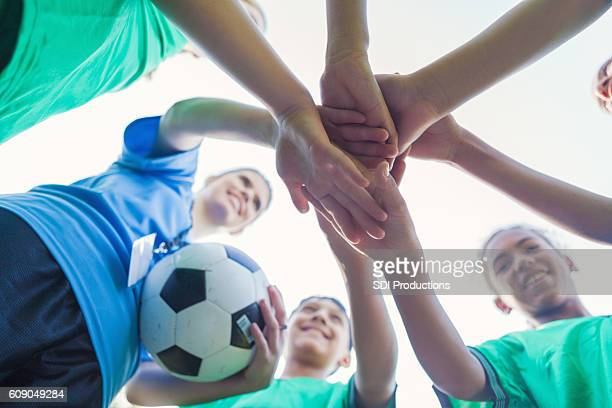 Group of diverse friends on soccer team huddling together
